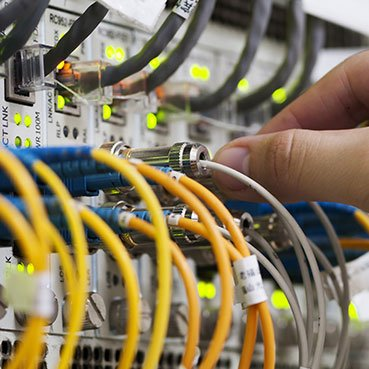 managed services person working with it networking cables